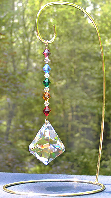 Bell 50mm Crystal With Rainbow Crystal Beads which Echo the Crystal Shape. Overall Length is 5.5 Inches. Shown with Medium Size Brass Ornament Stand, 8.5 Inches High.