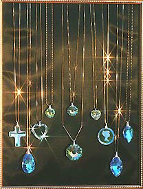 Display of Crystal Pendants on Gold Chains Sparkling in Sunlight